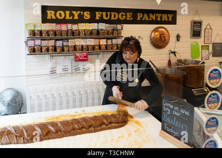 A fudge maker in Roly's Fudge Pantry in Stratford upon Avon making fudge in the traditional method by stirring the fudge with a paddle - Stock Image