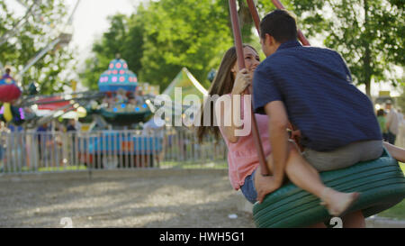 Blurred view of laughing happy boyfriend and girlfriend playing on tire swing in park - Stock Image
