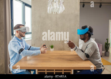 Young caucasian and african male web designers getting experience in working with 3D virtual reality glasses in apartment - Stock Image