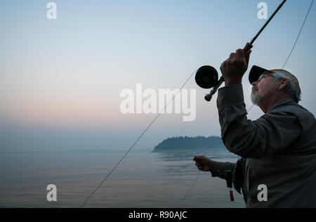 Senior Caucasian male fly fishing for salmon and sea run cutthroat trout in Puget Sound near Port Orchard, Washington USA - Stock Image