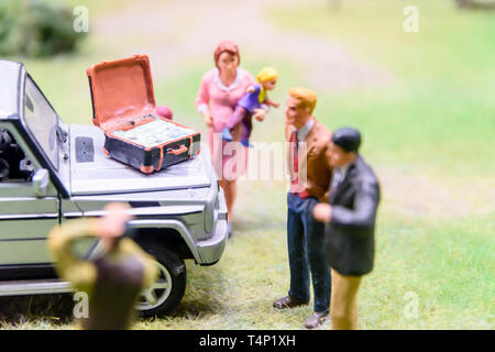 Miniature model of a family with a suitcase of cash on a car bonnet at Kolejkowo, Wrocław, Wroclaw, Wroklaw, Poland - Stock Image