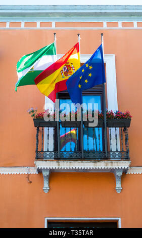 Left to right these flags are Andalusian, Spanish, and the flag of the European Union - Stock Image