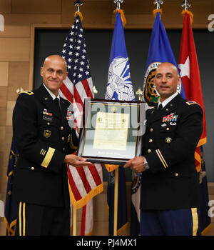 """Maj. Gen. Kirk Vollmecke, left, the Program Executive Officer for Intelligence, Electronic Warfare & Sensors, presents the Charter for Program Manager Position Navigation and Timing to Col. Nickolas T Kioutas, who took over the position. Kioutas is recent graduate of The Army War College in Carlisle, Penn. Before that, he was served at the Pentagon as the Chief of Staff for the Office of Process Innovation and Integration. Kioutas began his career in the Army Aviation, flying CH-47 Chinook helicopters. Vollmecke said Kioutas """"has extensive experience working with our teams starting with his ti - Stock Image"""