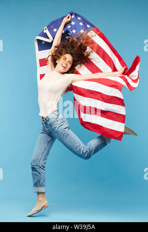 Happy young dynamic woman dancing in isolation with national American flag in raised hands - Stock Image