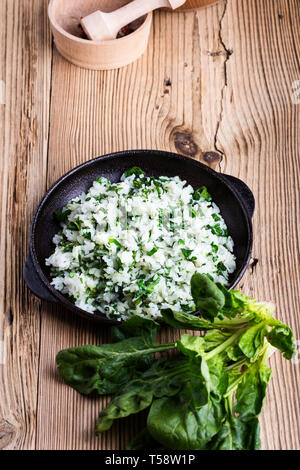 White rice with spinach served in cast iron skillet on rustic wooden table with fresh green leaf vegetables, plant based meal, close up, selective foc - Stock Image