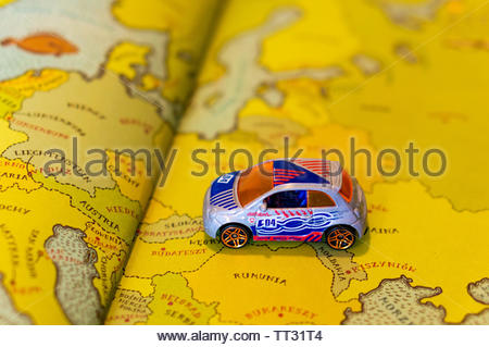 Mattel Hot Wheels Fiat 500 car on a European map from a open educational book on circa June 2019 in Poznan, Poland. - Stock Image