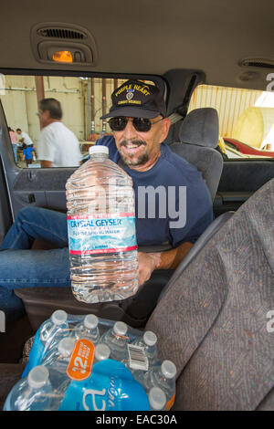 A war veteran collects water from a charity in Porterville supplying bottled water to houses who have had no running - Stock Image