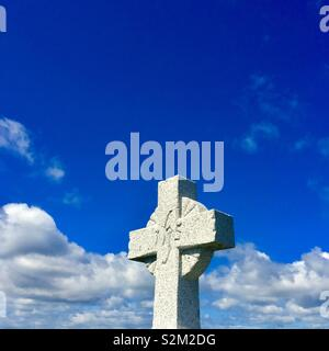 Cross Gravestone with sky in background - Stock Image