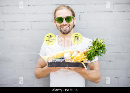Portrait of a handsome man holding box full of fresh vegetables on the brick wall background - Stock Image