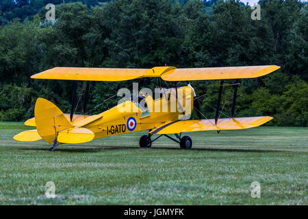 Yellow biplane Tiger Moth I-GATO replica from first world war on a meadow. - Stock Image