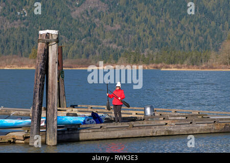 Middle aged woman in bright winter coat standing on a pier with kayak paddles. Grant Narrows Regional Park, Pitt Meadows, B.C., Canada - Stock Image