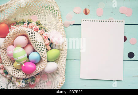 A beautiful and colorful close-up flat of easter eggs in plain pastel colors and striped in a basket with flowers by a notebook with blank space - Stock Image