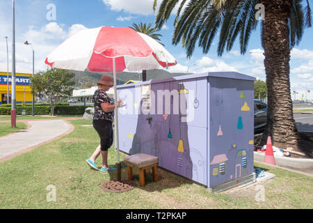 Lady volunteer adding artwork to electrical substation shielded from the sun in Tamworth Australia. - Stock Image