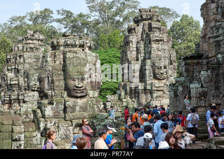 Tourists in Bayon Temple ruins in Angkor Wat. The Angkor Wat complex, Built during the Khmer Empire age, located in Siem Reap, Cambodia, is the larges - Stock Image