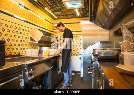 Entrepreneur with apron working in commercial kitchen at food truck - Stock Image