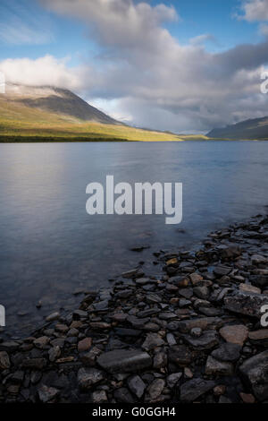 Mountains rise above lake Teusajaure, near Teusjaure hut, Kungsleden trail, Lapland, Sweden - Stock Image