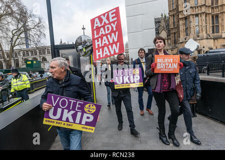 London, UK. 15th January 2019. UKIP members with a placard 'Axe Lady Haw Haw'.Groups against leaving the EU, including SODEM, Movement for Justice and In Limbo and Brexiteers Leave Means Leave and others protest opposite Parliament as Theresa May's Brexit deal was being debated.  While the two groups mainly kept apart, a small group, some in yellow jackets came to shout insults at pro-EU campaigners, while police tried to keep the two groups separate. Credit: Peter Marshall/Alamy Live News - Stock Image