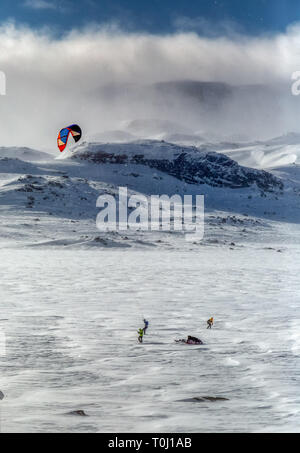 People kite skiing amongst the snow and ice in Norway. - Stock Image