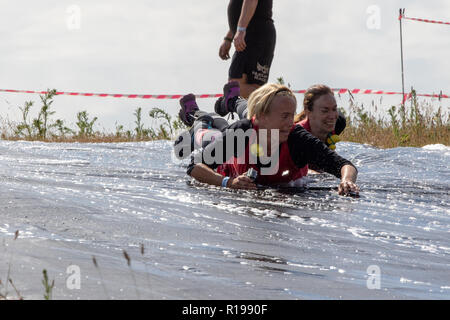 Sliding downhill on wet plastic - Stock Image