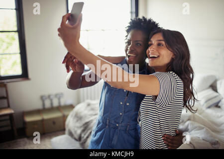 Smiling lesbian couple hugging, taking selfie with camera phone in bedroom - Stock Image
