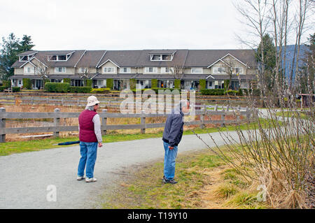 Senior Asian couple stopping to investigate some pussy willows along the path in Blakeburn Lagoons Regional Park, Port Coquitlam, B., C., Canada. - Stock Image