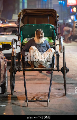 Vertical portrait a pulled rickshaw owner waiting for business in Kolkata aka Calcutta, India. - Stock Image