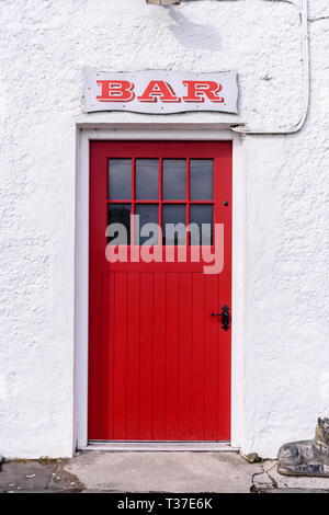 Sign above the red door at the entrance to an Irish pub. - Stock Image