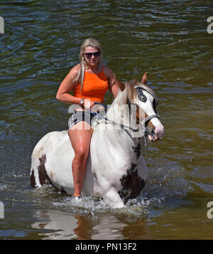 Gypsy Traveller girl riding horse in River Eden. Appleby Horse Fair 2018. Appleby-in-Westmorland, Cumbria, England, United Kingdom, Europe. - Stock Image
