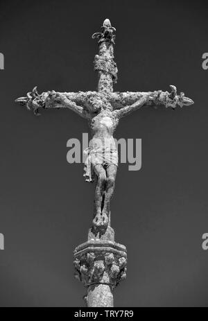 Monochrome picture of a stone statue of Christ on the cross at a cemetery in La Feuillée, Brittany, France. - Stock Image