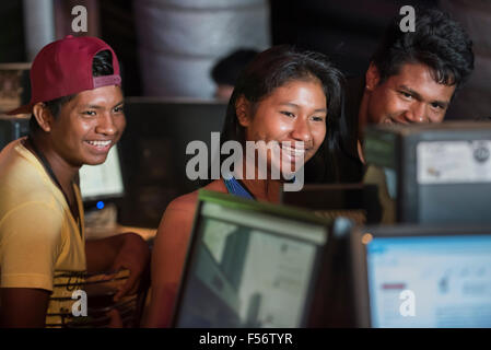 Palmas, Brazil. 28th Oct, 2015. Three young indigenous people share a funny Facebook post in the Digital House at - Stock Image
