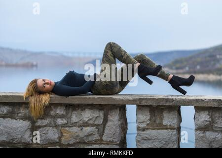 Young woman almost military clothing lying on back on wall ovelooking sea - Stock Image