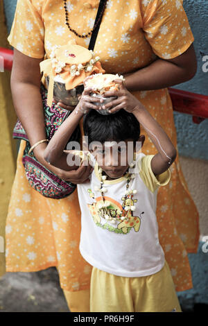 Young boy and his mother hold milk pots during Thaipusam festival at Batu Caves in Selangor, Malaysia - Stock Image