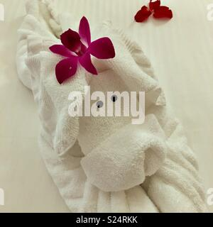 Hotel towel made into a dog with flowers - Stock Image