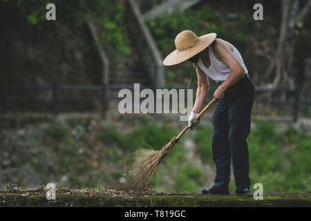 Hualien, Taiwan. 12th Jun, 2009. Daily life. Elderly man with a straw hat sweeps on top of old stone wall in Hualien, Taiwan. - Stock Image