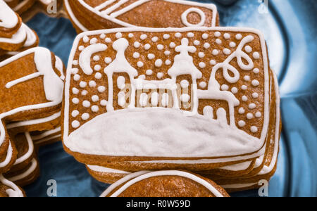 Close-up of a sweet Christmas gingerbread. Painted church. Beautiful detail of yummy aromatic pastries stacked on a plate. Decorated by white frosting. - Stock Image