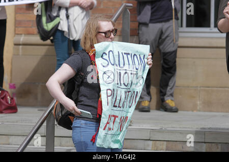 anActivists from the Climate Change group Extinction Rebellion holds a banner saying ÒSolution Not PollutionÓ during a demo outside Derby City Council house on 22/05/2019 - Stock Image
