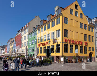 The waterfront restaurants in Nyhavn, Copenhagen, Denmark, attract many Copenhageners and tourists on a sunny spring - Stock Image
