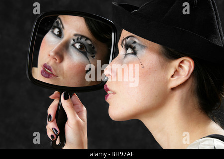 Young Woman Looking at Her Reflection in a Hand Mirror - Stock Image