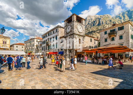Tourists sightsee, dine at cafes and shop under the clock tower in the Square of the Arms, in the medieval walled city of Kotor, Montenegro - Stock Image