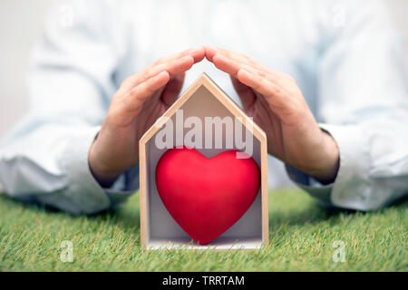 Wooden house with red heart on green grass protected by hands - Stock Image