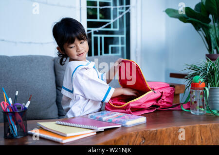 independent young kindergarten student preparing her own stuff before going to school in the morning - Stock Image
