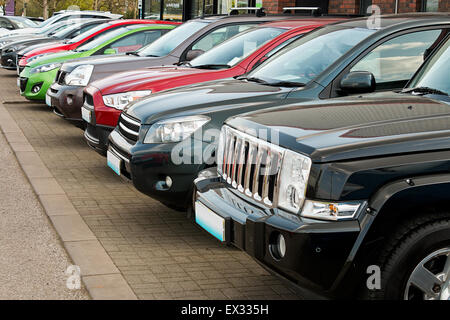 Row of used four by four motorcars also known as 4x4, SUV, off road, utility vehicle, ute or Station wagon arranged - Stock Image