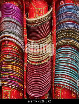 Colourful Indian bangles on display in a specially made carrying pouch. - Stock Image