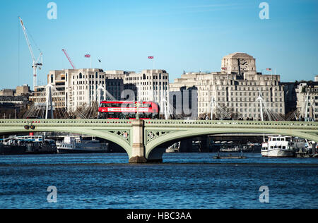 Modern red London bus on Westminster bridge on a winter's day looking towards the Embankment - Stock Image
