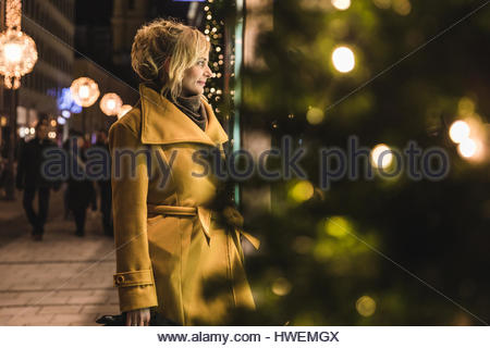 Mature woman christmas window shopping at night, Munich, Germany - Stock Image