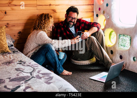 Adult couple enjoying technology at home or hotel traveling with looking a mobile phone device screen and using a laptop internet connected on the flo - Stock Image