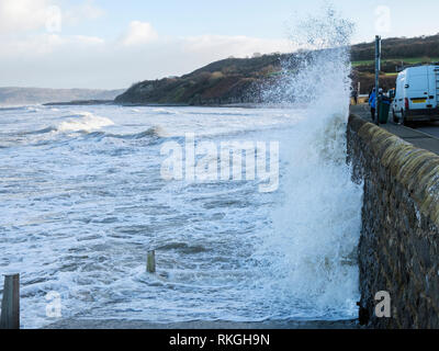 Rough sea and waves crashing against the sea wall on seafront during windy weather at high tide. Benllech, Isle of Anglesey, Wales, UK, Britain - Stock Image