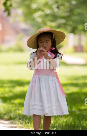 Young girl playing flute at Williamsburg, Virginia, USA - Stock Image
