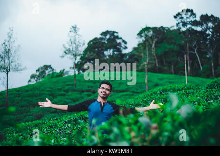 Casual male portrait smiling in the centre of the tea plantation representing healthy and happiness - Stock Image