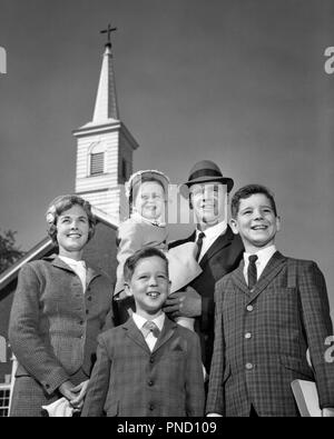 1960s FAMILY PORTRAIT MOTHER FATHER TWO SONS ONE DAUGHTER IN ARMS CHRISTIAN CHURCH SPIRE BEHIND THEM - c9375 HAR001 HARS HUSBAND DAD MOM CLOTHING FACES NOSTALGIC PAIR COMMUNITY SUBURBAN MOTHERS EXPRESSION OLD TIME NOSTALGIA BROTHER OLD FASHION SISTER 1 JUVENILE FACIAL STYLE BEST SONS PLEASED JOY LIFESTYLE FIVE RELIGION CELEBRATION FEMALES MARRIED 5 SUNDAY BROTHERS RURAL SPOUSE HUSBANDS HEALTHINESS HOME LIFE UNITED STATES COPY SPACE FULL-LENGTH HALF-LENGTH LADIES DAUGHTERS PERSONS INSPIRATION UNITED STATES OF AMERICA MALES CHRISTIAN SIBLINGS SPIRITUALITY SISTERS EXPRESSIONS FATHERS B&W - Stock Image